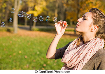 Blowing bubbles into the wind - Beautiful yopung brunette...