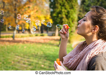Blowing bubbles into the wind. - Beautiful yopung brunette...