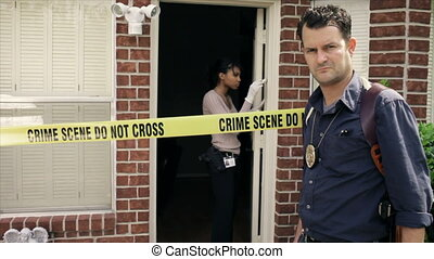 Detective at Crime Scene Looking - A detective standing in...