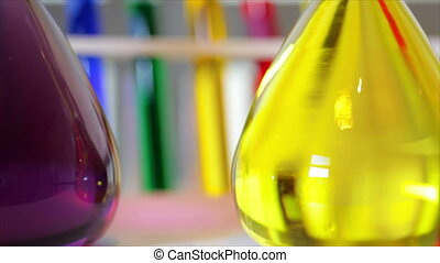 bright colored liquids in lab flask - The camera dollies...