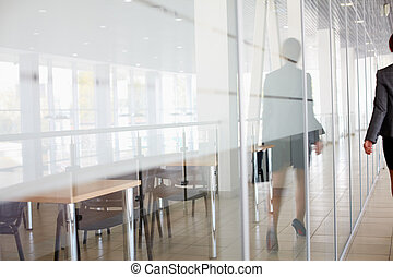 Walk in corridor - Reflection of businesswoman walking along...
