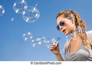 Blowing bubbles ot the sky. - Gorgeous young brunette girl...