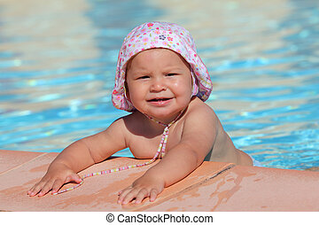 Cute toddler girl playing in a swimming pool