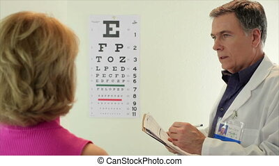 Optometrist having his patient read - An optometrist has his...
