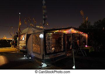 Caravan on campsite illuminated in the evening