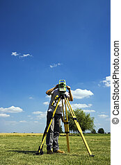 Behind Theodolite - land surveying in rural area