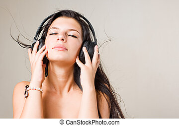 Brunette immersed in music. - Gorgeous young brunette...