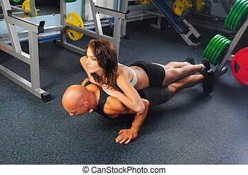 man and a woman in the gym - man and a woman trained in the...