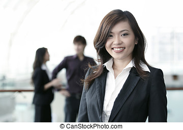Business woman with colleagues in the background - Asian...