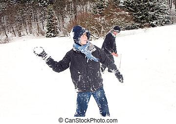 Simon wirft einen Schneeball Kinder auf der Rodelbahn in...