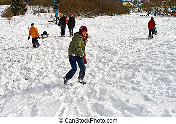 children have a snowball fight in the white snowy area -...
