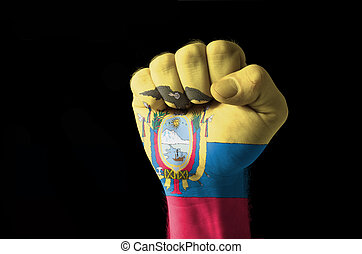 Fist painted in colors of ecuador flag - Low key picture of...