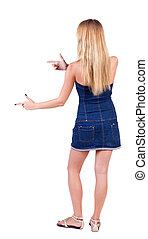 back of view beautiful young woman in jeans dress pointing...