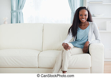 Woman sitting on sofa with legs crossed - Smiling woman...