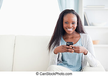 Woman in living room with her phone - Smiling woman in...