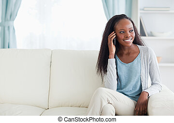 Woman phoning on sofa