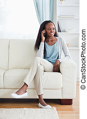 Woman with cellphone on sofa