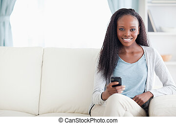 Woman typing text message on the sofa