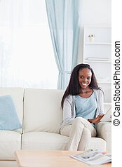 Woman with tablet on couch - Smiling woman with tablet on...