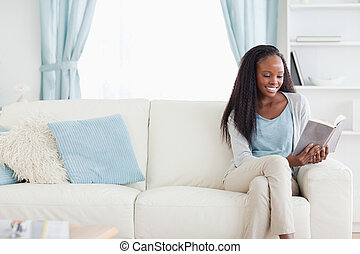 Woman reading a book in living room - Smiling woman reading...