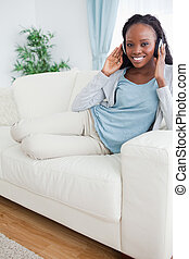 Woman relaxing on couch with music - Smiling woman relaxing...
