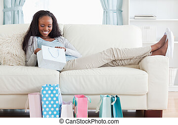 Woman on couch checking her shopping