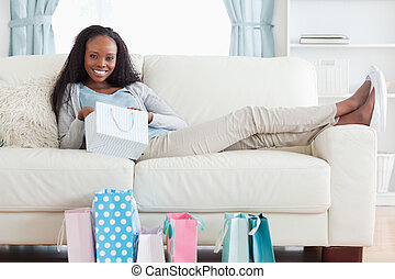 Young woman putting her feet up after shopping - Smiling...
