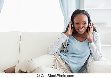 Woman relaxing on couch with headphones on - Smiling woman...