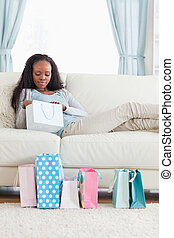 Woman on sofa checking her shopping