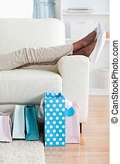 Woman on couch putting her feet up - Young woman on couch...