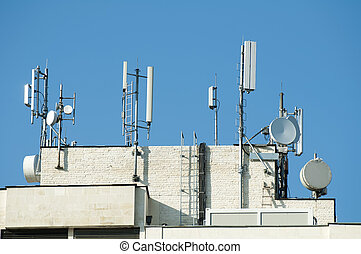 GSM transmitters on a roof of white administrative building....