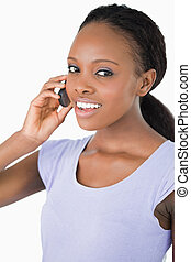Close up of smiling woman talking on the phone against a white background