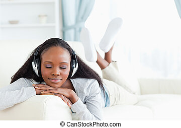 Woman with closed eyes enjoying music - Young woman with...