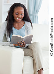 Woman with book on couch