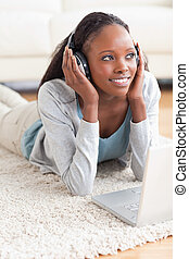 Close up of smiling woman lying on the floor with her notebook listening to music