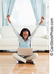 Woman stretching while sitting on the floor with her laptop