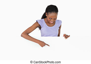 Woman looking at what she is pointing at on white background...