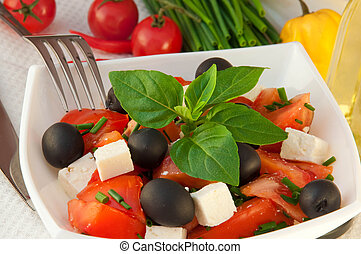 Salad from tomatoes, olives and the cow cheese, a fork with...