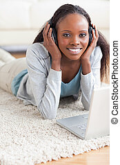 Close up of smiling woman lying on the floor with her laptop listening to music