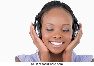 Close up of smiling young woman listening to music with...