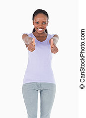 Close up of thumbs up being given by woman on white background