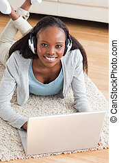 Close up of smiling woman lying on the floor with notebook listening to music