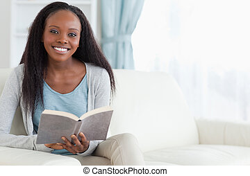 Woman on couch with book - Smiling woman on couch with book