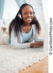 Close up of smiling woman lying on floor with her notebook listening to music