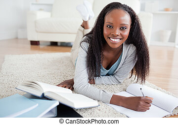 Woman lying on the floor studying - Smiling woman lying on...