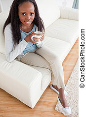 Woman enjoying coffee on sofa