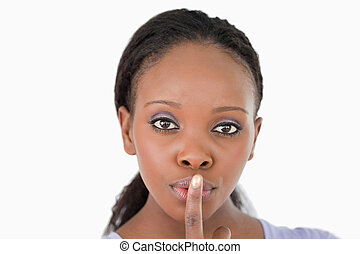 Close up of woman demanding silence on white background -...