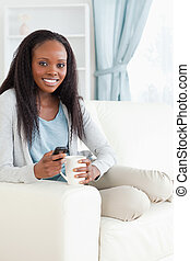 Woman writing text message while having a coffee - Smiling...