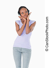 Close up of woman enjoying music with headphones on white background