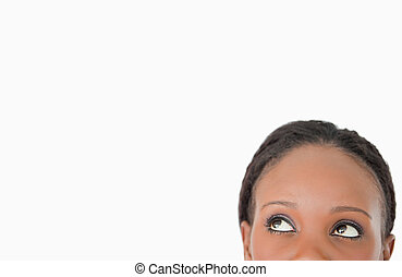 Close up of young woman looking upwards diagonally on white...